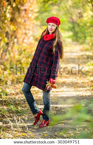 Portrait of attractive young caucasian woman in warm colorful clothing on yellow leaves outdoors smiling - stock photo