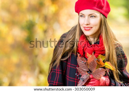 Portrait of attractive young caucasian woman in warm colorful clothing on yellow leaves outdoors smiling, copy space - stock photo