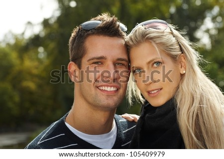Portrait of attractive young couple in park, smiling. - stock photo