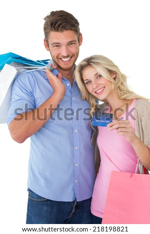 Portrait of attractive young couple with shopping bags and credit card over white background - stock photo