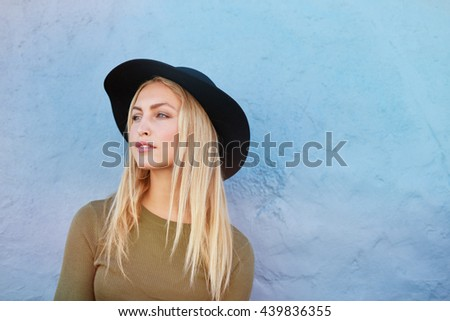 Portrait of attractive young female model with hat looking away against blue wall. Caucasian young blond woman with copy space. - stock photo