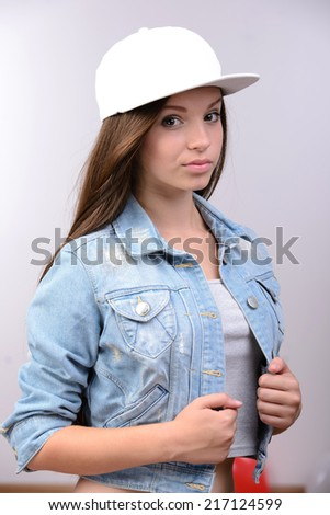 Portrait of attractive young girl in baseball cap, smiling at camera - stock photo
