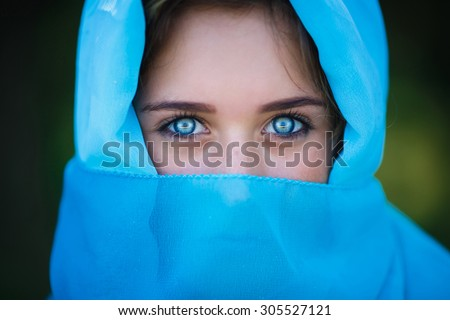 Portrait of attractive young girl in blue sari covered her head in a forest - stock photo