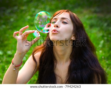 portrait of attractive young girl inflating colorful soap bubbles outdoor - stock photo