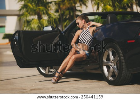portrait of attractive young happy woman in the new car - outdoors. Portrait of beautiful young woman with makeup in fashion clothes on nature. Beautiful women driving a car wearing accessories - stock photo