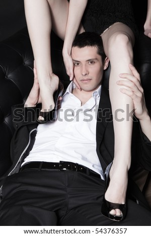 Portrait of attractive young man embracing woman's perfect legs - stock photo