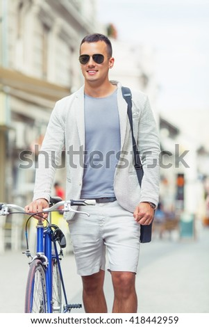 Portrait of attractive young man is walking down the street with his bicycle beside him. He is going to work. He is wearing a suit and sunglasses. Young businessman is looking away and smiling. - stock photo