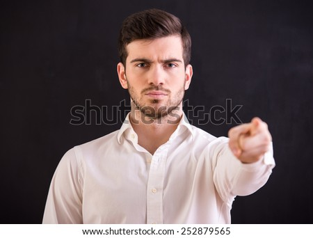 Portrait of attractive young man points his finger at the camera on dark background. - stock photo
