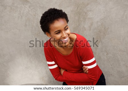 Portrait of attractive young modern black woman laughing with arms crossed