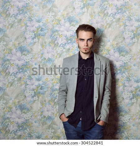 Portrait of attractive young mysterious man looking at camera, over floral background. Image toned. - stock photo
