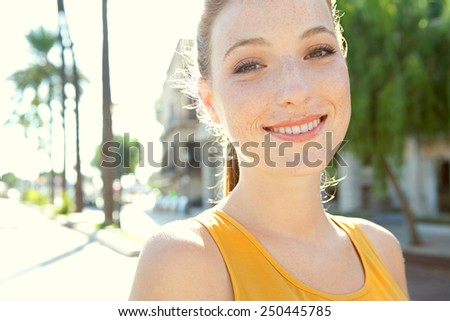 Portrait of attractive young smiling tourist woman visiting a sunny destination city with the sunshine filtering through her on a hot summer holiday trip. Travel and discovery, smart lifestyle. - stock photo