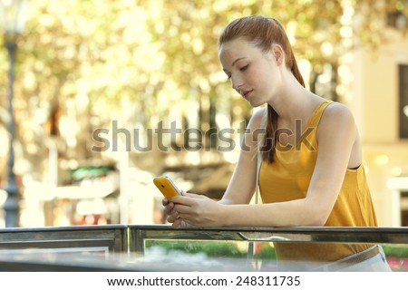 Portrait of attractive young tourist woman in a destination city holding and using a smart phone device during a sunny summer holiday trip. Travel and technology lifestyle outdoors. - stock photo