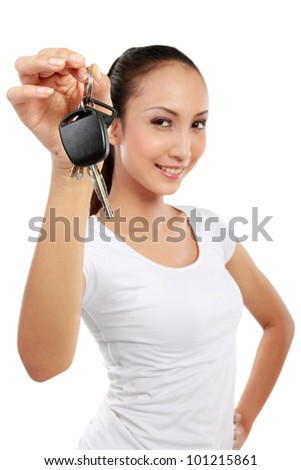Portrait of attractive young woman holding car key isolated over white background - stock photo