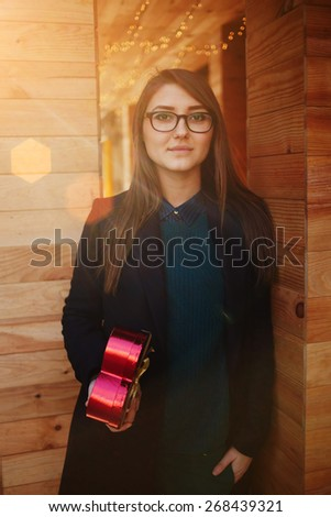 Portrait of attractive young woman holding heart shaped gift box presented by her boyfriend - stock photo
