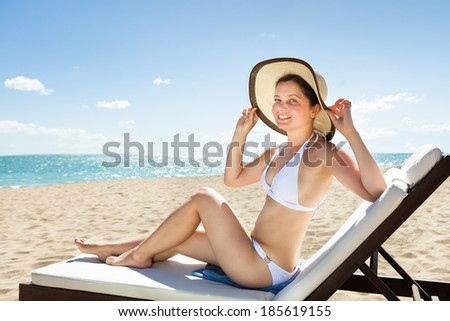 Portrait of attractive young woman in bikini relaxing on deck chair at beach