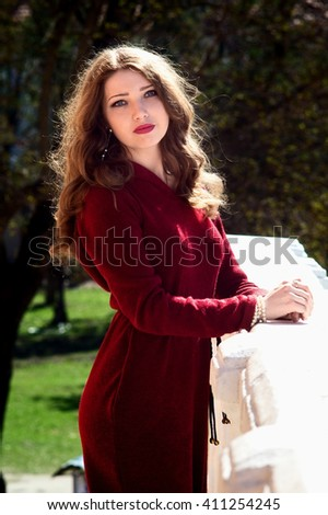 Portrait of attractive young woman in bright red dress in sunlight.Green background