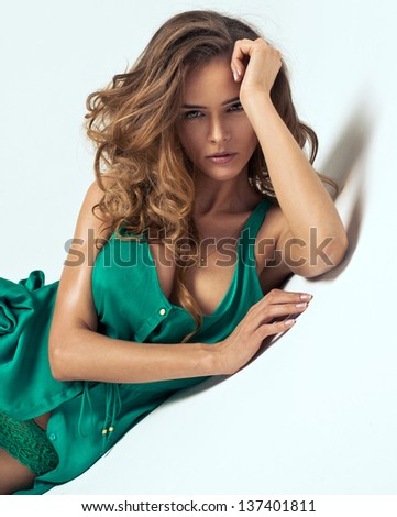 Portrait of attractive young woman in green dress with decolletage - stock photo