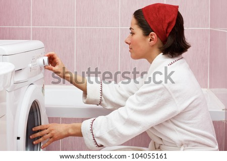 Portrait of attractive young woman in robe, starting her washing machine in her bathroom - stock photo