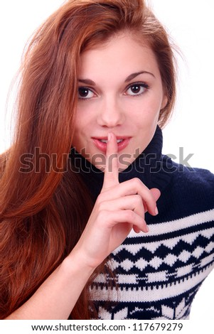 Portrait of attractive young woman in sweater showing silence gesture