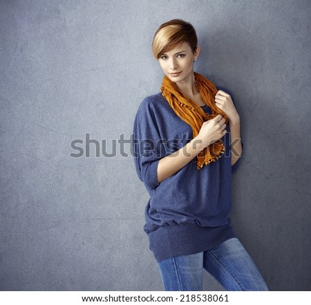Portrait of attractive young woman leaning to wall, smiling. - stock photo
