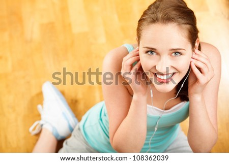 Portrait of attractive young woman listening to music at gym - stock photo
