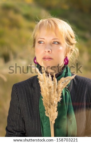 portrait of attractive young woman, on a background autumn leaves