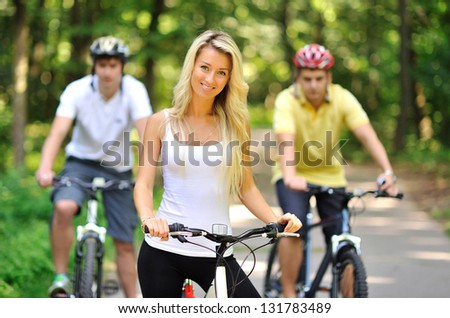 Portrait of attractive young woman on bicycle and two men behind her - stock photo