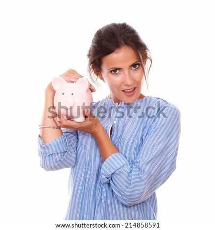 Portrait of attractive young woman on blue blouse with her piggy savings, standing and looking at you on isolated studio - stock photo