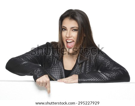 Portrait of attractive young woman pointing over white background - stock photo