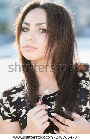 Portrait of attractive young woman posing outdoors - stock photo