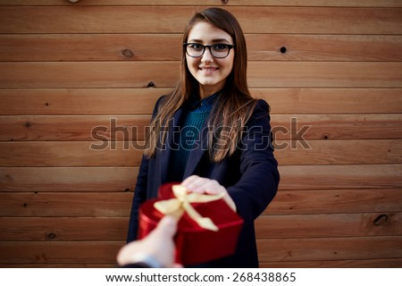 Portrait of attractive young woman receives or takes a shape heart gift from her boyfriend - stock photo