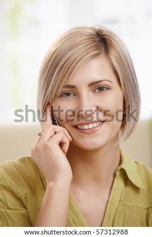 Portrait of attractive young woman speaking on mobile phone at home, smiling at camera. Copyspace on left.?