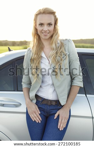 Portrait of attractive young woman standing by car at countryside - stock photo