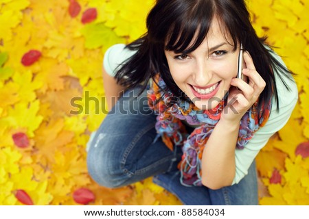 portrait of attractive young woman talking on the mobile phone and sitting on a carpet of yellow and red fallen leaves - stock photo