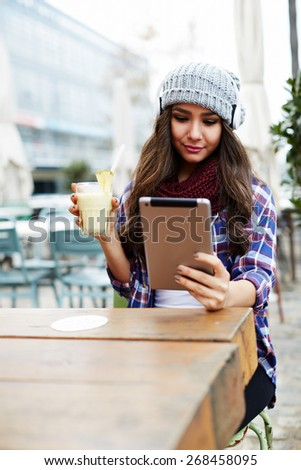 Portrait of attractive young woman using digital tablet while sitting in coffee shop, cute hipster girl enjoying a drink cocktail while sitting at a sidewalk cafe in the city, student read e-book - stock photo