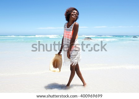 Portrait of attractive young woman walking in water by beach   - stock photo