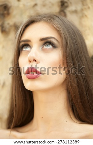 Portrait of attractive young woman with bare shoulders and bright make up looking away standing in broad daylight outdoor on natural stone background, vertical picture - stock photo