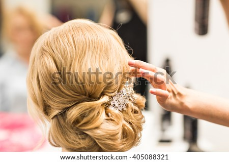 Portrait of attractive young woman with beautiful hairstyle and stylish hair accessory, rear view.