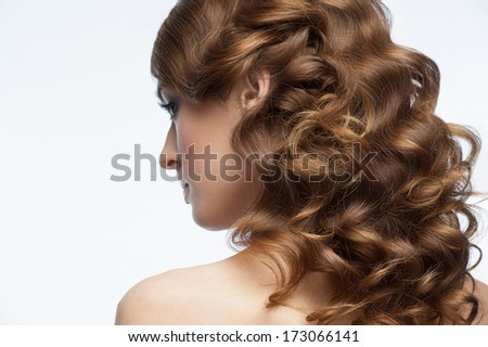 Portrait of attractive young woman with beautiful hairstyle. Girl with long curly hair, rear view - stock photo