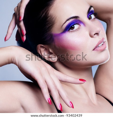 Portrait of attractive young woman with colorful makeup on face - stock photo