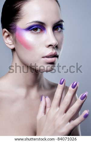 Portrait of attractive young woman with colorful makeup on face and painted finger nails; studio background. - stock photo