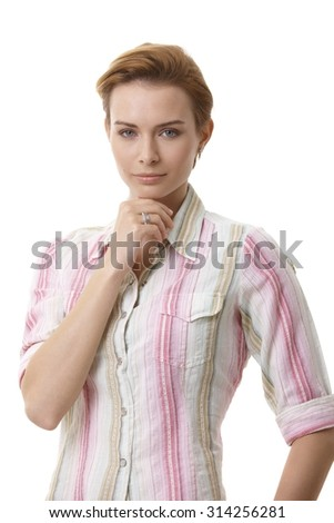 Portrait of attractive young woman with hand on chin, looking at camera. - stock photo