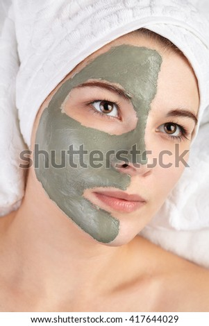 Portrait of attractive young woman with mud clay mask. Spa beauty procedures skin care treatment concept. White salon towels background - stock photo