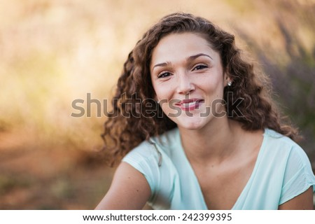 Portrait of Attractive Young Woman with Olive Skin and Curly Hair - stock photo