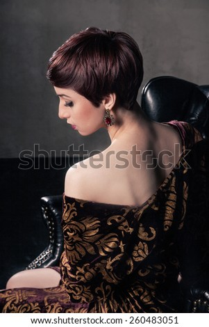 Portrait of  attractive young woman with short dark hair and beautiful hairstyle. Rear view. - stock photo