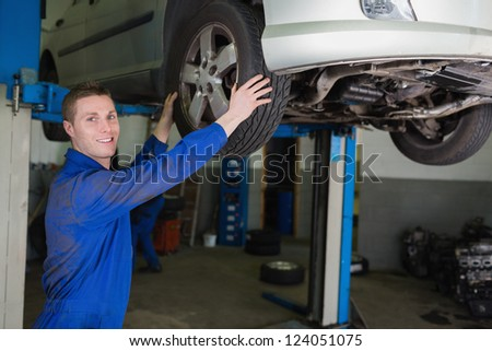 Portrait of auto mechanic adjusting car tire in garage