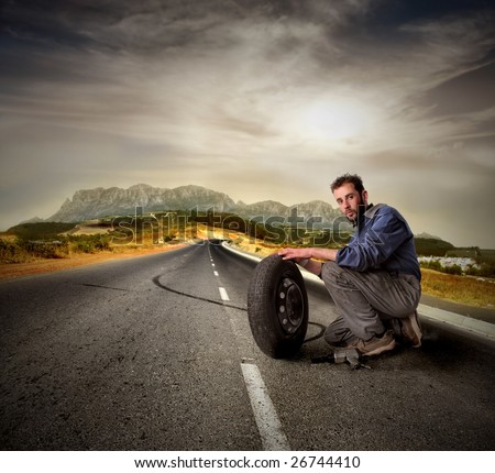 Portrait of auto mechanic with wheel on a country road - stock photo