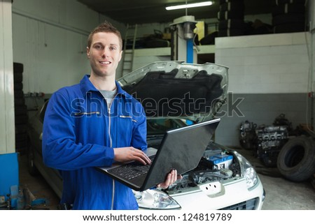 Portrait of auto mechanic working on laptop in workshop