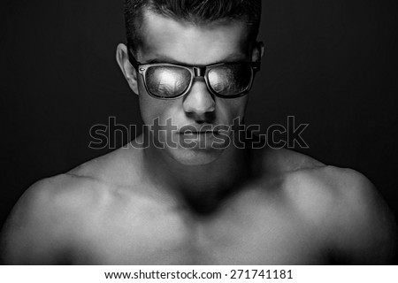 Portrait of awesome male model with naked muscular body. Isolated on dark grey background.