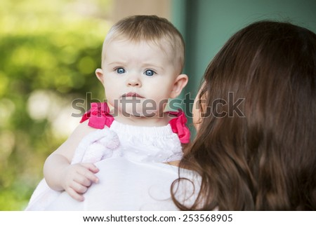 portrait of baby being held by brunette woman - stock photo